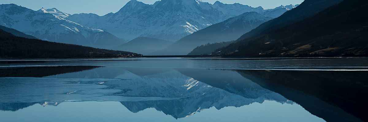 calm body of lake between mountains