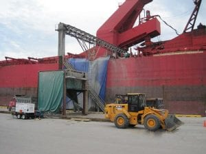 Custom built box conveyor built for offloading goods from large container ship next to skid steer loader