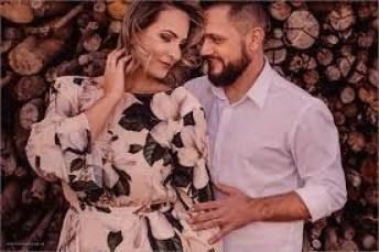 Casal posando para a foto em frente a uma pilha de lenha, foto espontânea resultado de técnicas de direção de pessoas, fotografia Robison Kunz