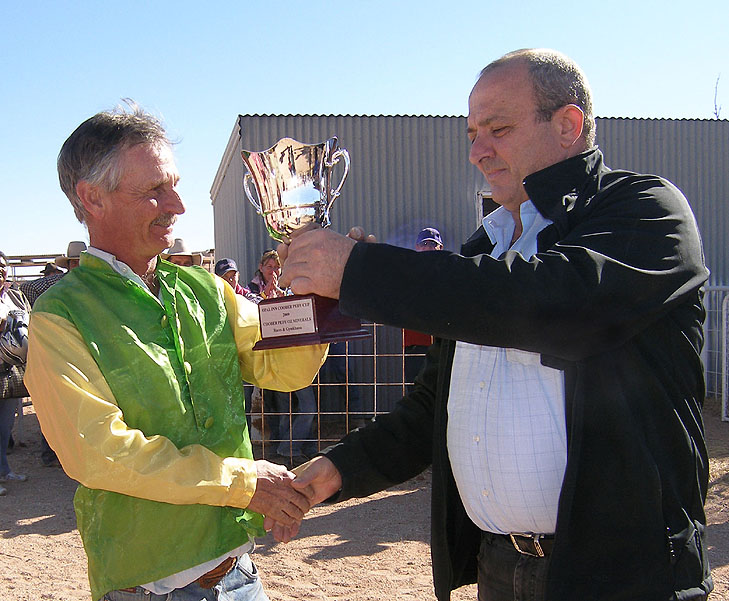 Winning Jockey Garry Burchmore received his trophy from Robert Coro of the Opal Inn