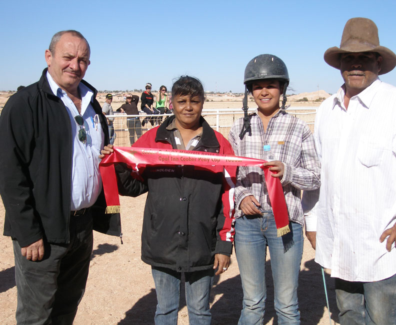 """Robert Coro presents second place ribbons to """"Taken Charge"""", L-R Colleen Taylor, Jockey Gemma Hunt and Ronald Boland"""