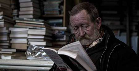 uomo legge libro biblioteca
