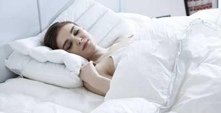 donna giovane dorme letto bianco