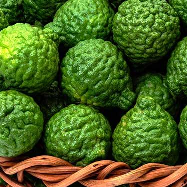 un cesto di bergamotti verdi disposti l'uno sopra l'altro