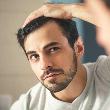 Un ragazzo preoccupato per la perdita di capelli verifica lo scalpo tirando indietro la chioma con una mano.