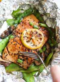A foil packet of salmon topped with black sesame seeds and a lemon slice, open with a fork taking a bite.