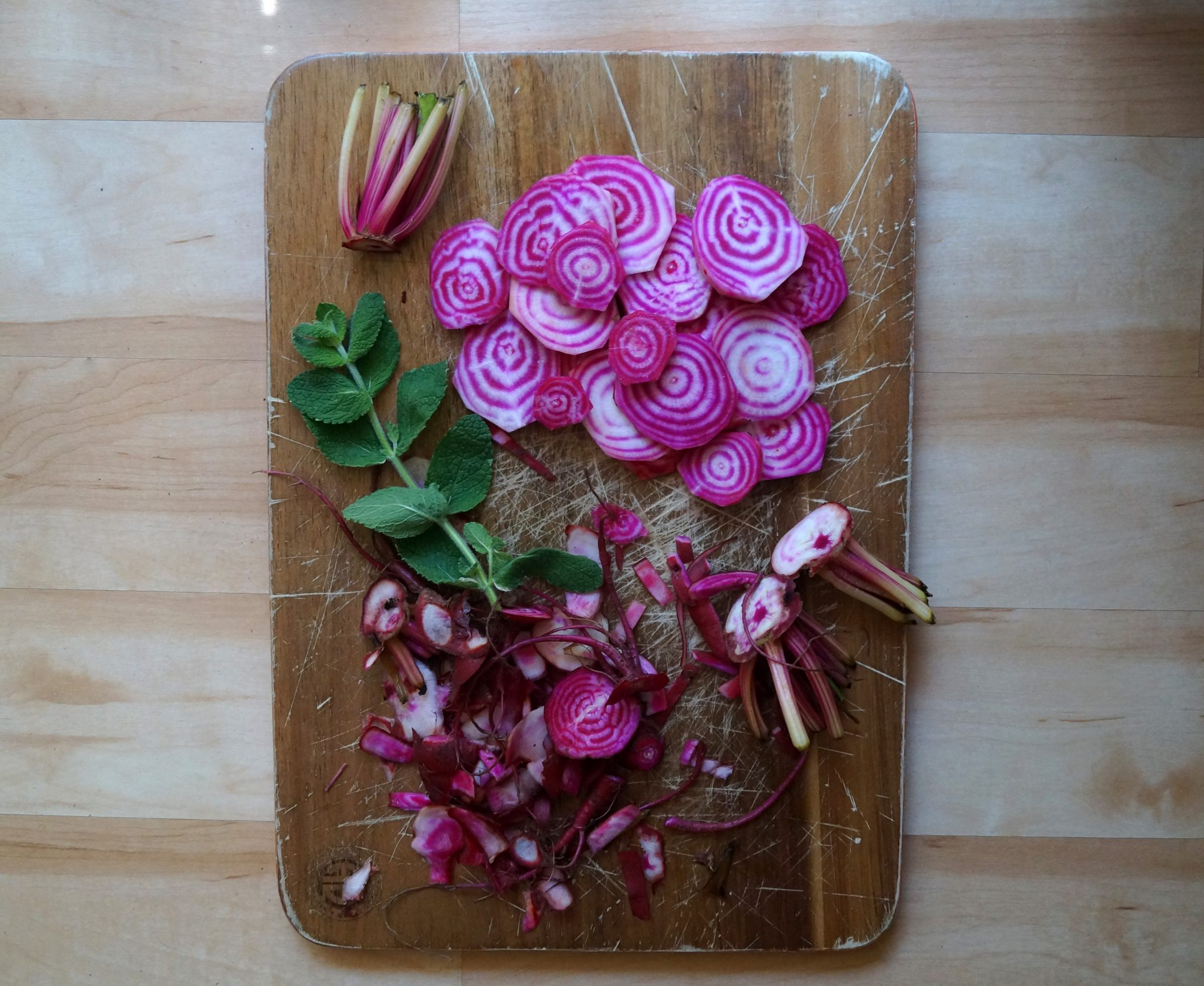 Sliced beets and mint on a small cutting board.
