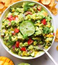A white bowl filled with mango guacamole, garnished with lime and cilantro.