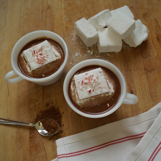Two small white cups filled with hot cocoa and topped with homemade marshmallows and crumbled candy canes.