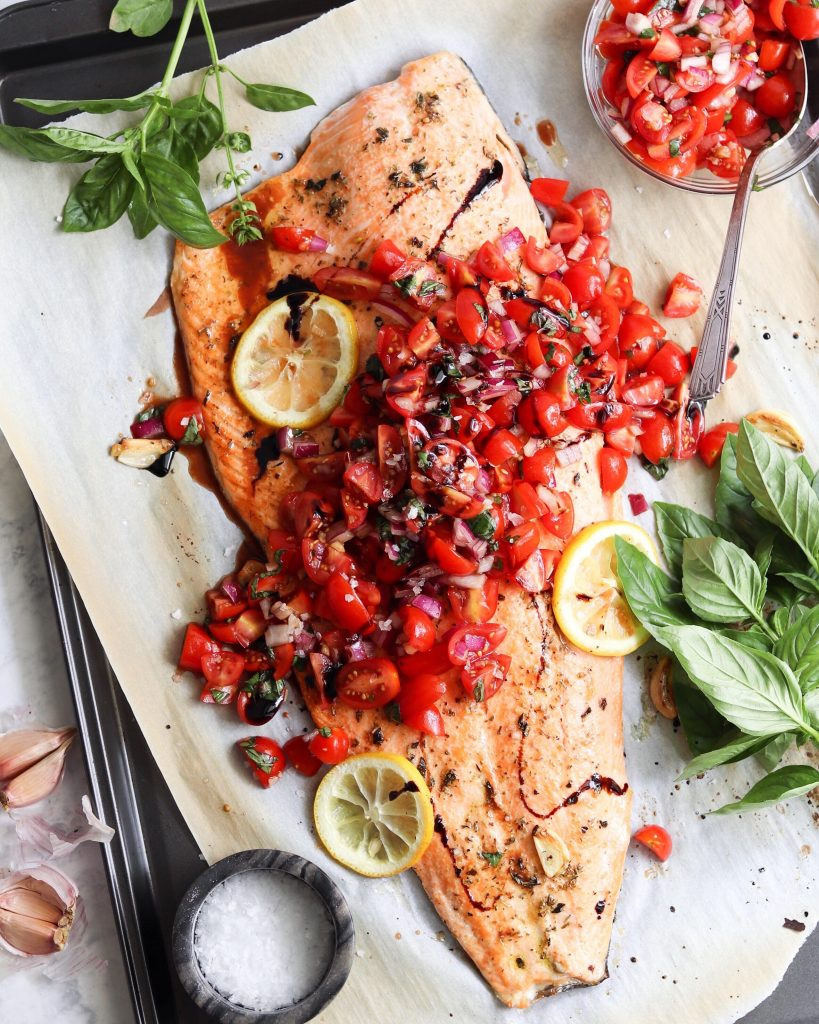 Roasted Salmon on a sheet pan topped with the Bruschetta.