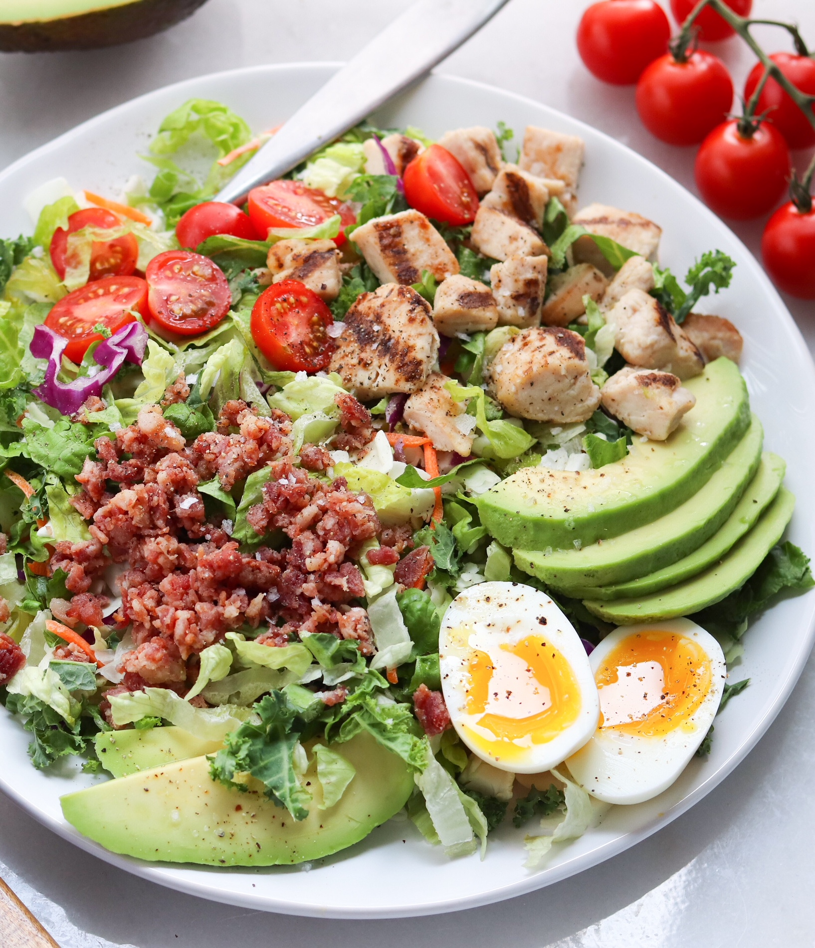 Close up of the finished salad topped with eggs, tomatoes, and avocado on a large white plate.