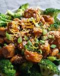 Orange Sesame Chicken and broccoli, plated and topped with sesame seeds.