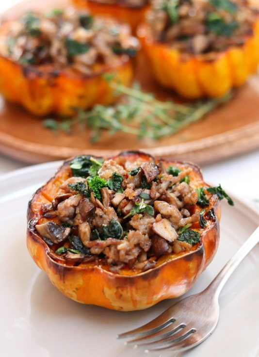 One serving of the roasted acorn squash half in stuffed with ground sausage, kale, and mushrooms. It sits on a white plate with a fork.