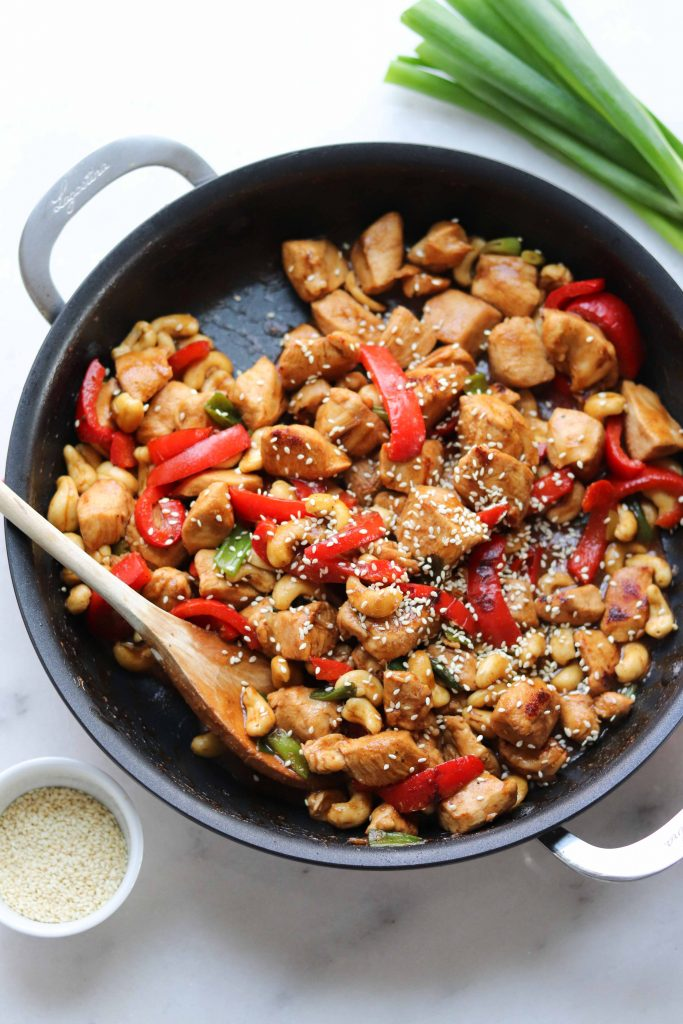 Whole30 compliant Kung Pao Chicken is served in a large skillet. The sticky sauce is mixed in and it's topped with sesame seeds. A small bowl of extra sesame seeds sits beside the skillet.