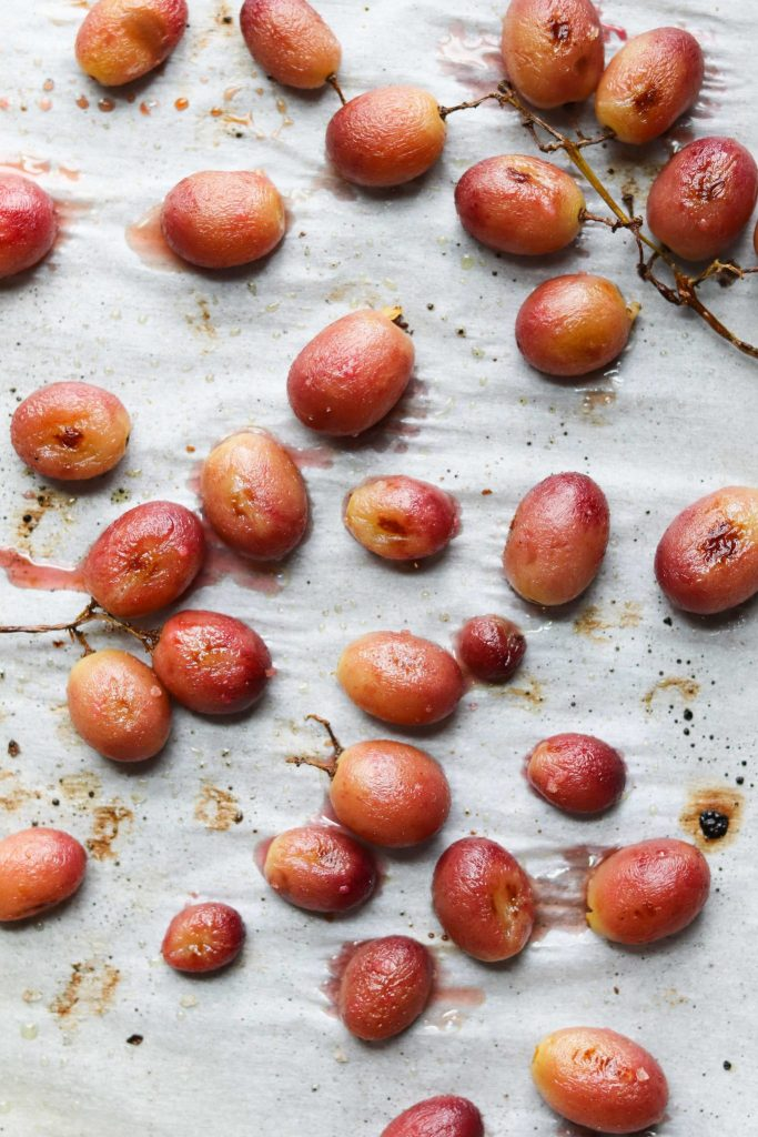 Roasted Grapes scattered and cooling on a baking sheet.
