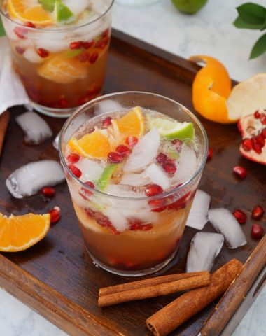 Whole30 Holiday Kombucha Mocktail in glass with ice and garnished with fruit, Finished