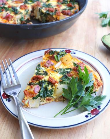 A slice of frittata is on a small plate with parsley for garnish and a fork