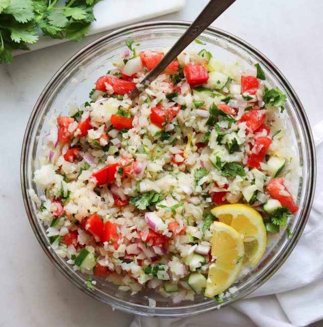 Whole30 cauliflower tabbouleh made with cauliflower rice, tomatoes, herbs, lemon, garlic, cucumbers, and topped with lemon wedges.