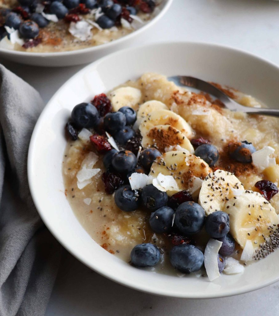Side view of a bowl filled with grain free porridge that's topped with blueberries, banana slices, and flaked coconut.