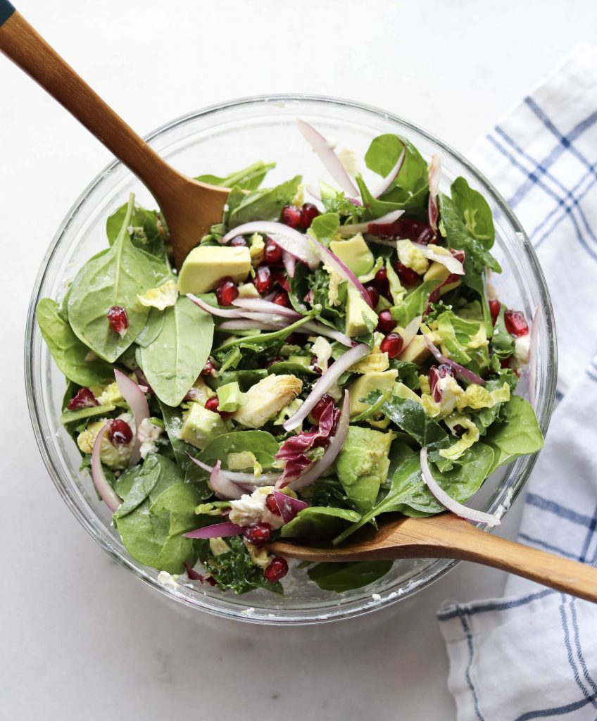 The finished winter salad with avocado, spinach and pomegranate, all mixed in a glass bowl.