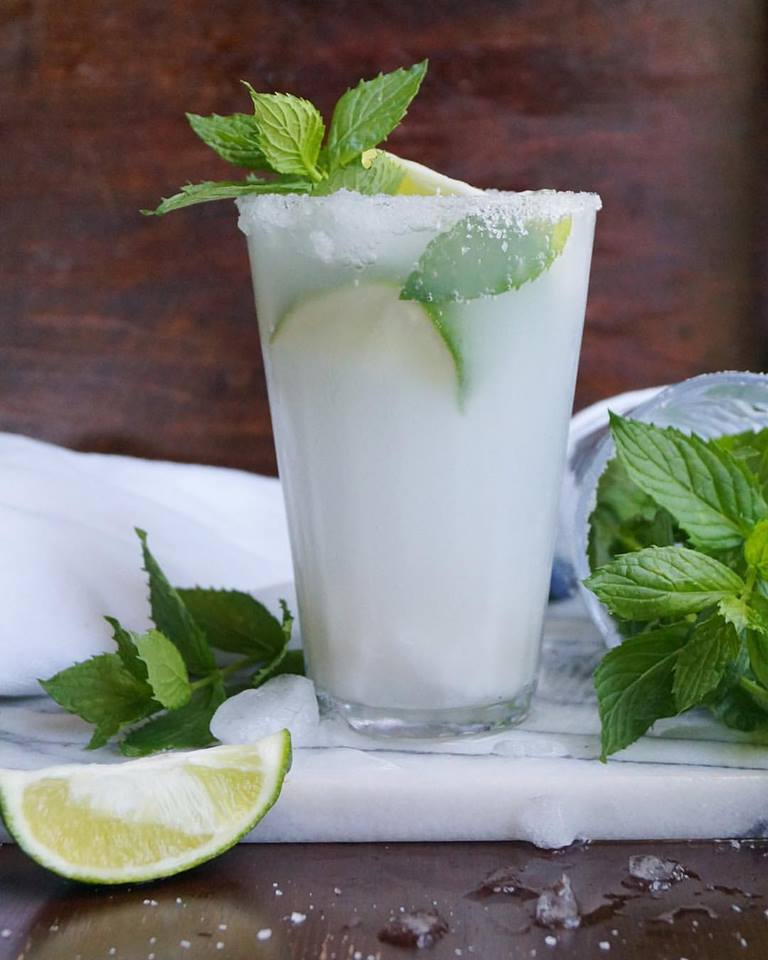 Tall glass filled with Coconut Mojito Mocktail, garnished with lime and mint
