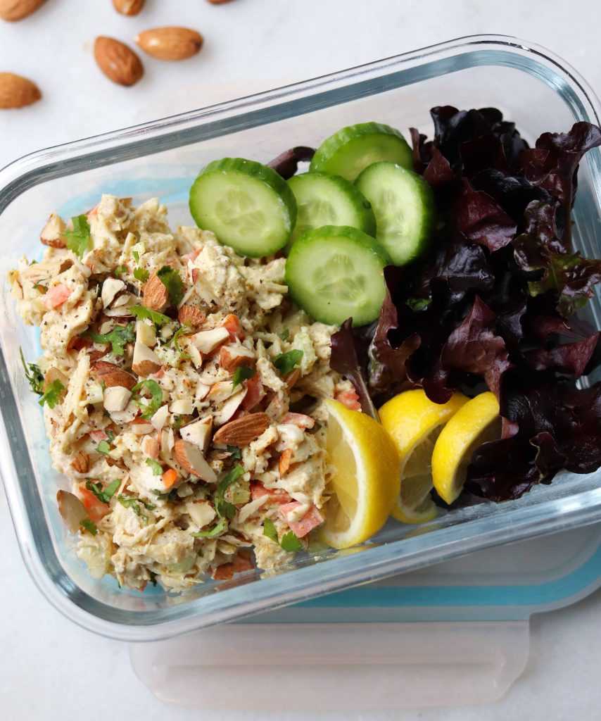 Whole30 Curry Chicken Salad with Carrots served in a glass meal prep container. The chicken salad is sprinkled with chopped almonds and fresh cilantro and served with sliced cucumbers, lemons, and fresh lettuce.