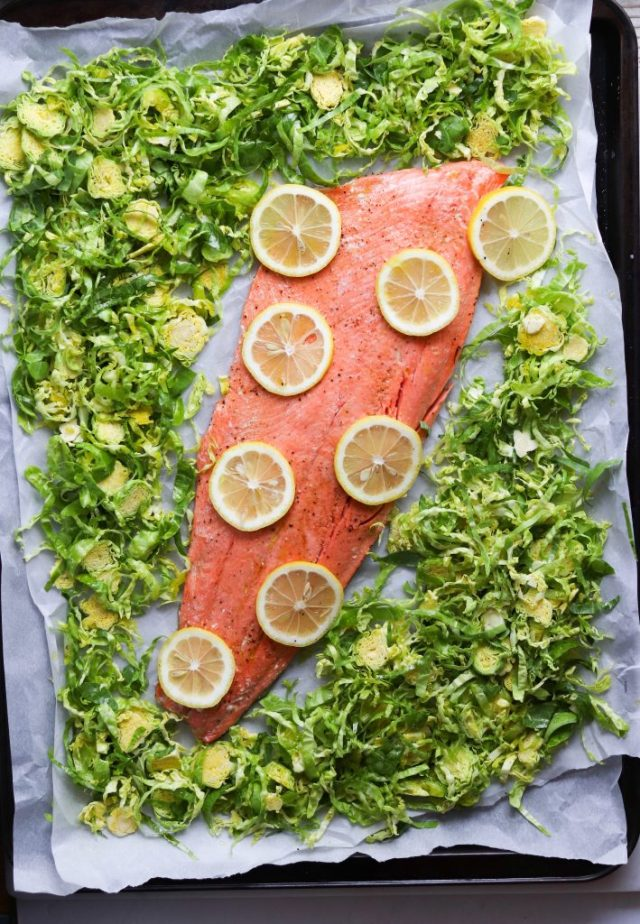 The uncooked salmon and wilted brussels sprouts salad is laid on a large sheet pan. The salmon is topped with slices of lemon and the Brussels sprouts are arranged around the salmon.
