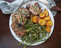 A large white platter with grilled pork chops, grilled garlic scapes, and grilled sliced peaches.