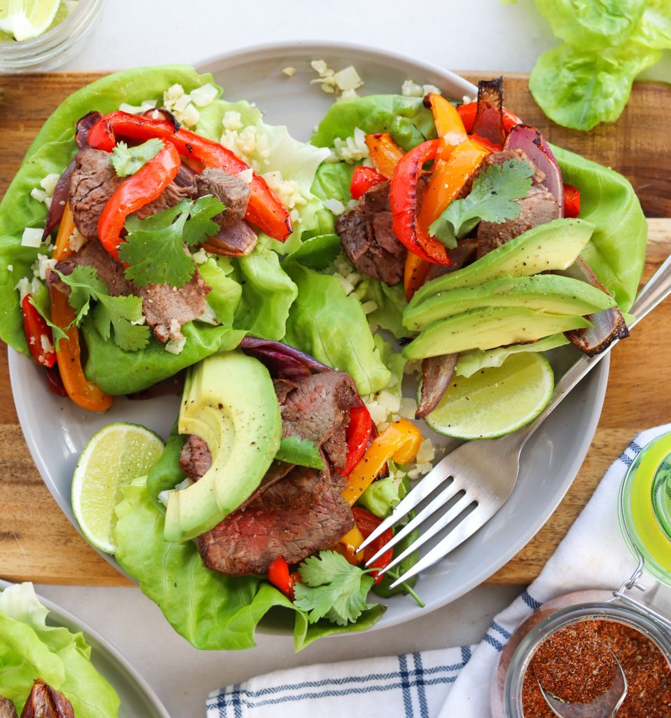 Whole30 Fajitas with avocado and bell peppers served inside lettuce wraps, finished.