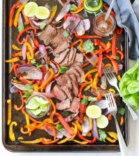 Whole30 sliced steak fajitas cooked and served on a sheet pan with mixed vegetables and lime slices