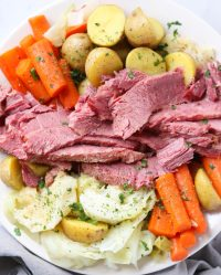 Close up of sliced corned beef and cooked veggies on a white plate.