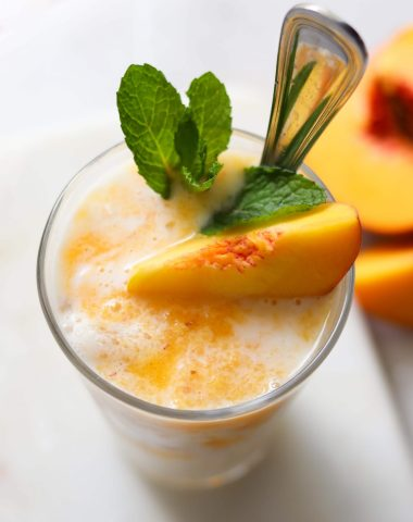 The finished drink in a tall glass, garnished with a slice of peach and mint leaves.
