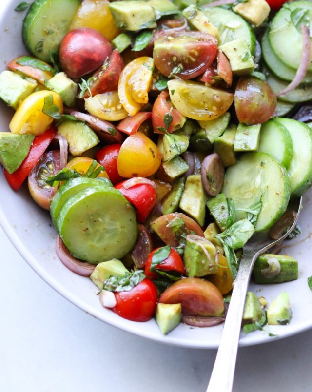 The Whole30 Tomato, Cucumber and Avocado Salad, all mixed up in a gray bowl. The vegetables are drizzled with the vinaigrette and sprinkled with a little salt. A serving spoon is in the mixture, ready to serve up some deliciousness onto your plate!