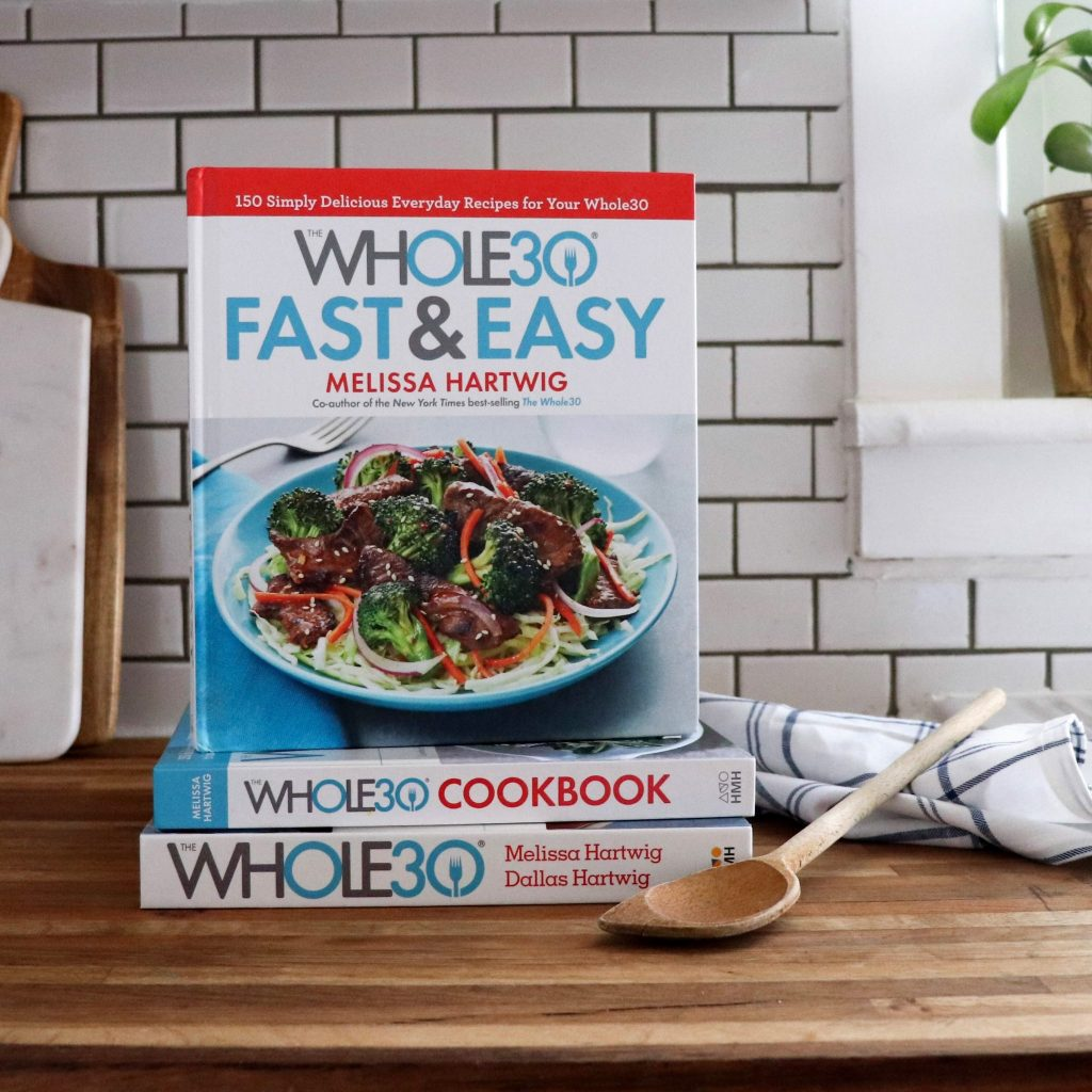 Whole30 Fast & Easy Cookbook sitting on a butcher block countertop. Behind it is a white tile backsplash.
