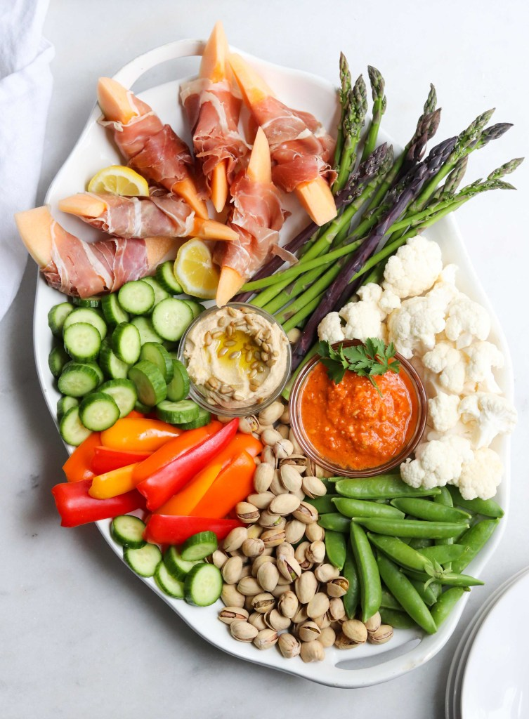 A large white platter filled with pistachios, snap peas, raw veggies, and dips.
