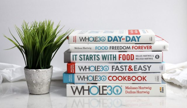 The first six Whole30 books, laying in a stack on a white marble board. Beside it is a small potted plant with grass growing out of it.