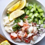 Whole30 Lobster Tail Salad, served in a white bowl with diced celery, mayo, shallots, and garnished with lemon slices.