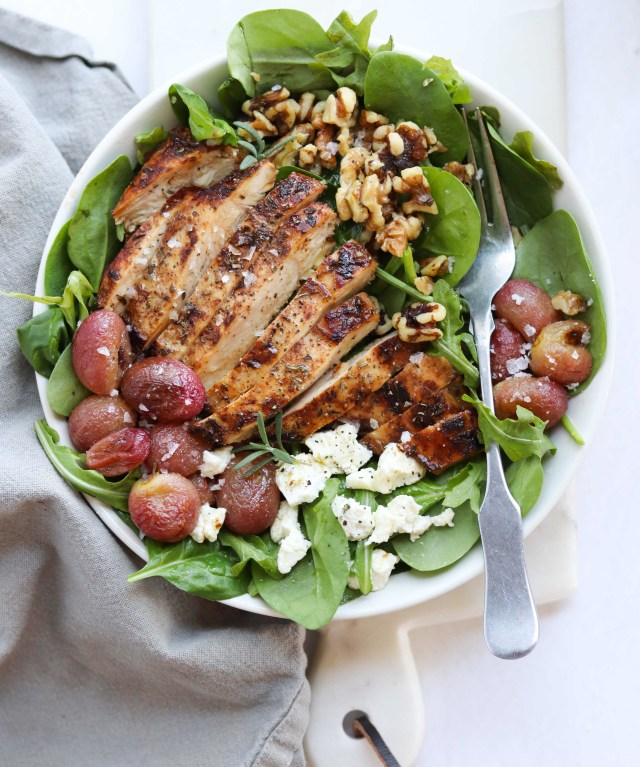 Finished dish. A white bowl filled with spinach and topped with sliced grilled chicken, walnuts, and roasted grapes, with a fork and dark grey napkin.