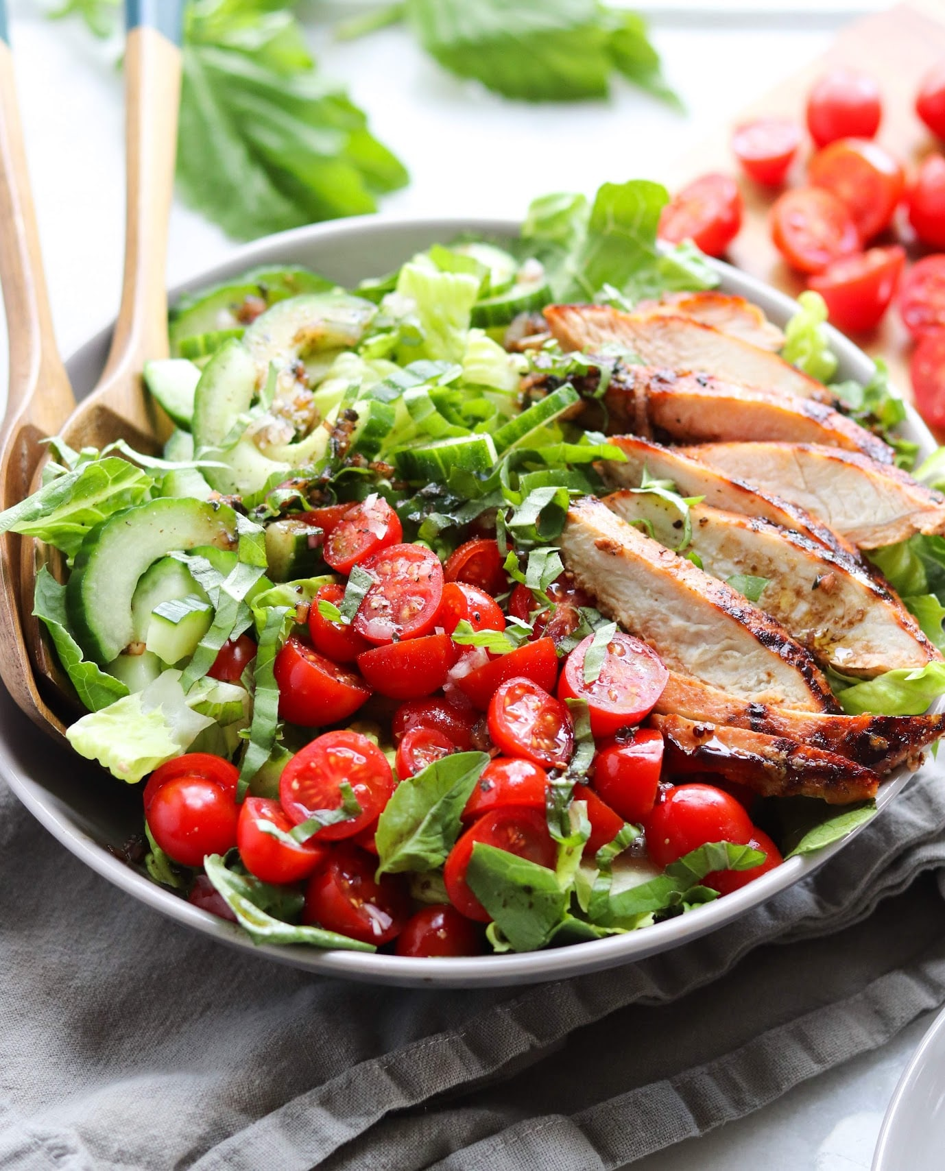 A gray bowl filled to the brim with chopped romaine lettuce, sliced grilled tomato-basil marinated turkey breasts, fresh cherry tomatoes, and sliced cucumbers. Two large wooden serving spoons are in the dish, ready to mix and serve the salad!