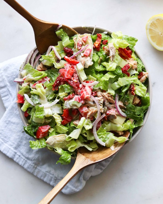 Tossed Mediterranean Salad, finished dish in a gray bowl on a white marble board. Two large wooden serving spoons are tossing the salad.