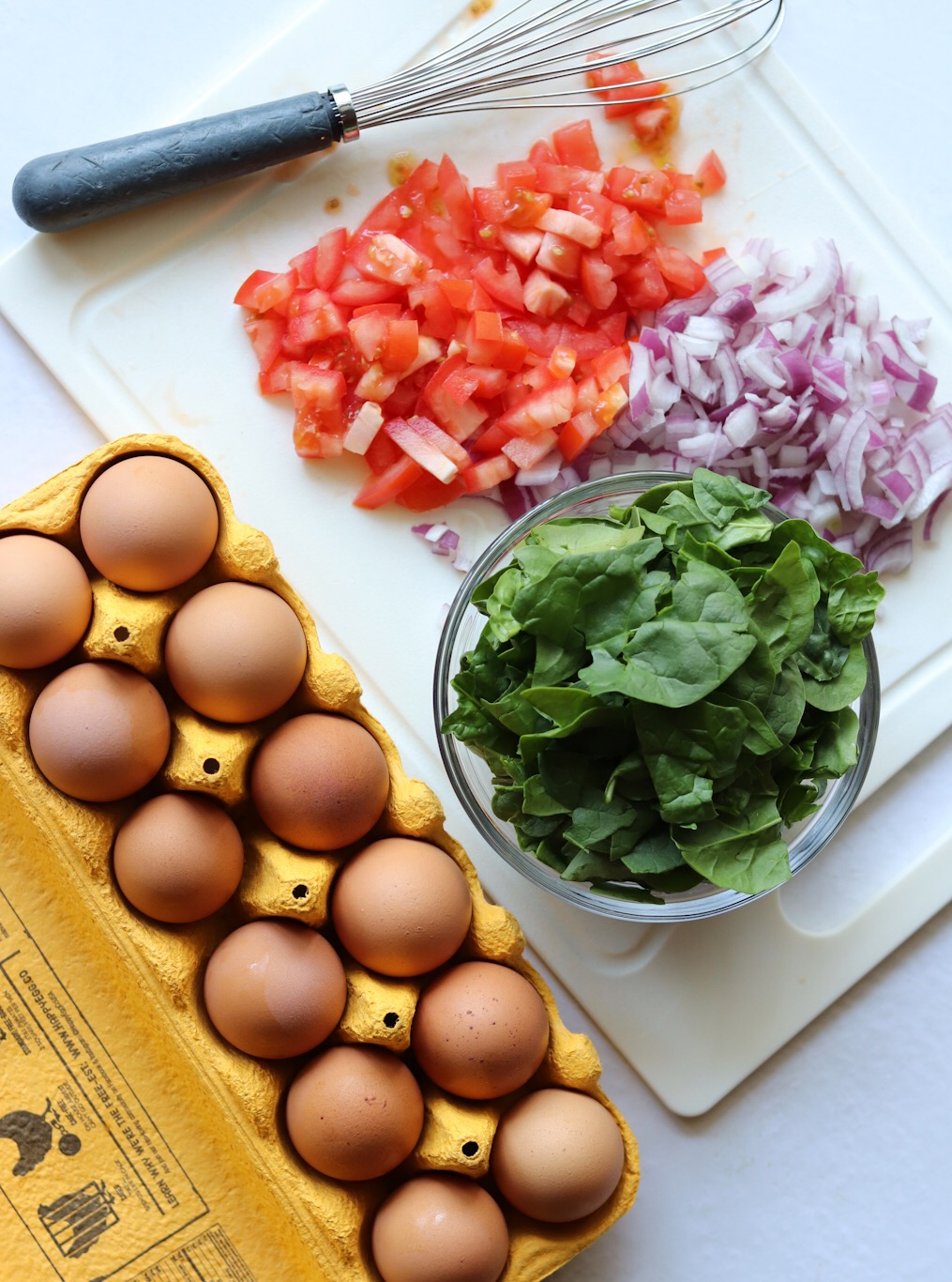 Casserole Ingredients: Eggs, a small glass bowl of baby spinach, and a plastic cutting board with diced onions and tomatoes.