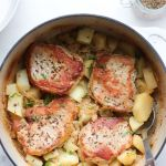 "Close up of finished dish in the dutch oven with the text ""Whole30, Dutch Oven German Pork Chops"" for Pinterest"