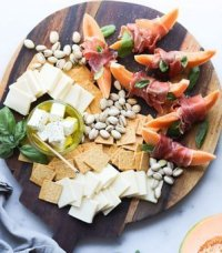 A wooden cutting board lays on a white marble board topped with prosciutto wrapped melon, sliced cheddar cheese, pistachios, and gluten free crackers.