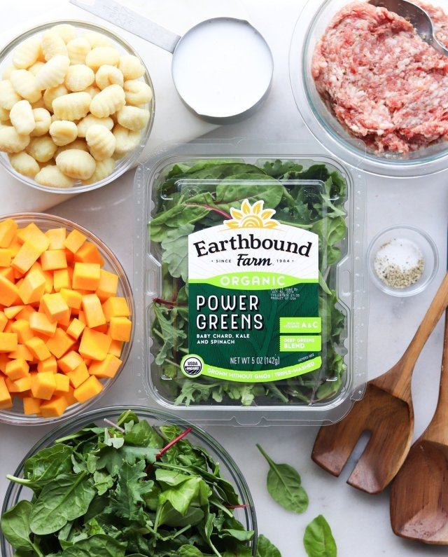 All the ingredients laid out on a white marble board. Gnocchi, ground sausage, diced butternut squash, coconut milk, salt and pepper, and power greens.