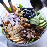 The Grilled Chicken Salad plated in a large glass bowl with the lemon dijon salad dressing being drizzled on top.