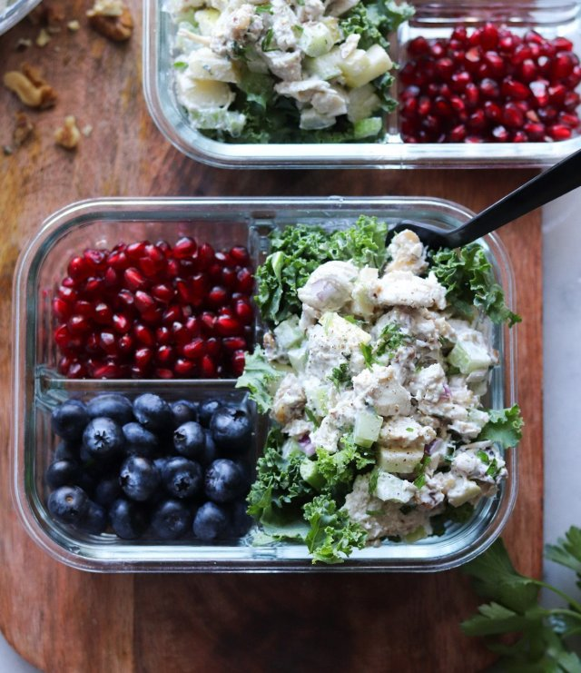 Close up top down of the finished Paleo chicken salad in a glass meal prep container with a black plastic fork.