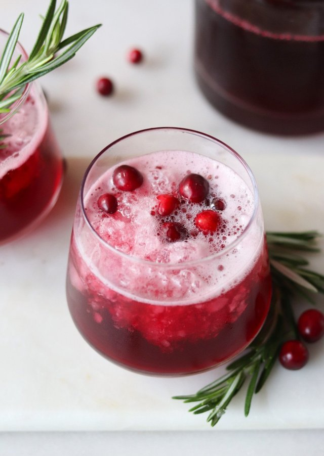 A small glass on a white board filled with the finished mocktail and garnished with cranberries.