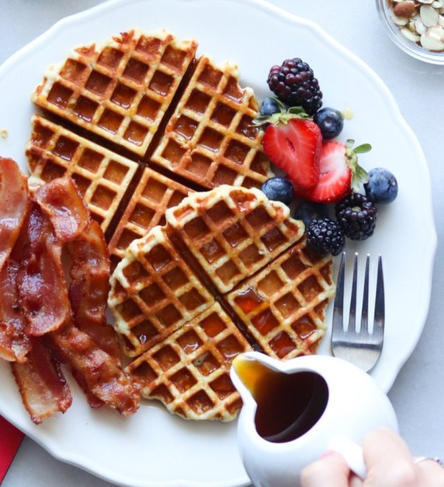 Waffles on a white plate surrounded by berries. A hand is pouring maple syrup on top.