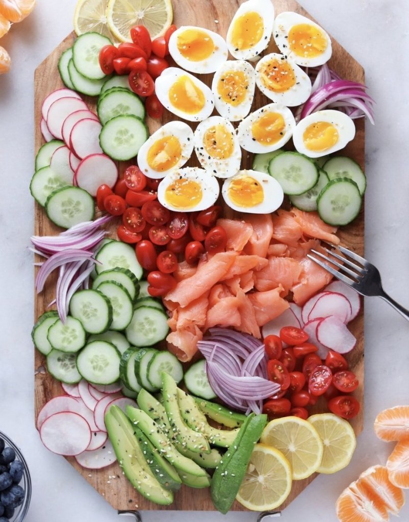 A wooden platter on a white board with smoked salmon, cut vegetables, and boiled eggs.