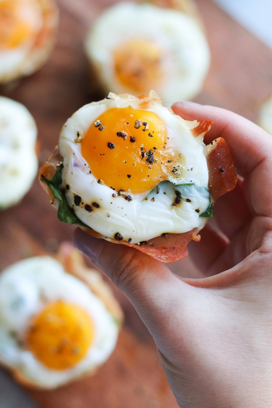 Close up top down photo of a hand holding a finished whole30, keto prosciutto egg cup after it comes out of the air fryer.